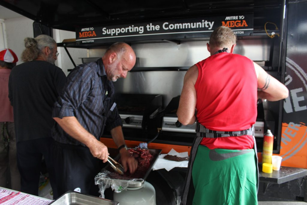 Volunteers cook some Christmas meats on the barbecue supplied by Mitre 10 Mega. PHOTO/EMILY NORMAN
