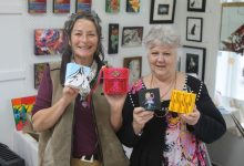 Heart of Arts volunteers Dra McKay and Doreen Finlay holding up some of the little artworks in the exhibition. PHOTO/EMILY NORMAN
