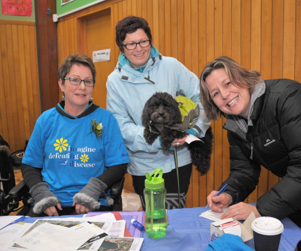 Liz Anderson has Sarah Jones and dog Quigley and Kylie Henricksen of Masterton supporting the cause at the MND charity auction and walk at Lakeview School on Sunday. Pooches were popular on the walk with dozens turning up for the stroll around Henley Lake.
