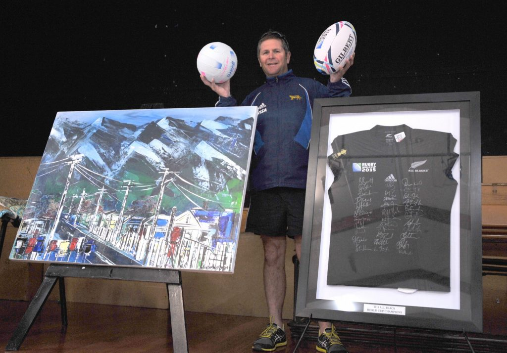 Auctioneer Brian Diamond with items under the hammer at Lakeview School for MND NZ including three paintings by Marie Kjestrup Evans which raised $4200 and an All Black jersey signed by the World Cup winning team from Sam Whitelock which went for $3700.