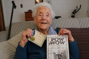 Mildred Turley holding one of her husband Trevor's service medals, a card that was attached to a parcel sent by the British Red Cross to POWs, and the volume of the POW WOW journal which contained Trevor's obituary.