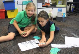 Juliana Larsen Forster and Skye Carlton working together on a maths problem in a Akonga Maori class.
