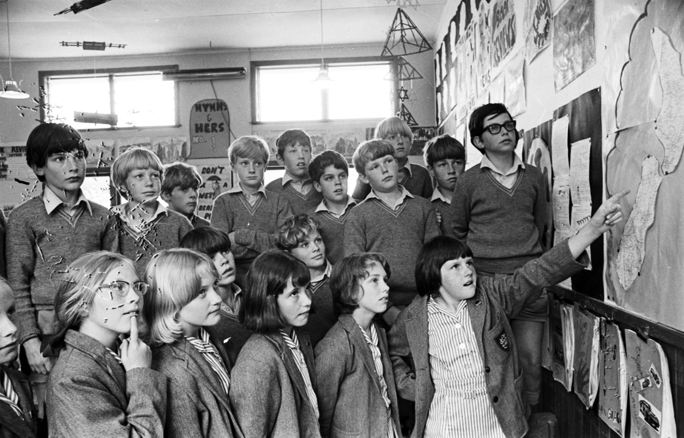 This photo, which appeared in the Times-Age on November 17, 1971, shows Standard Four pupils of Hadlow pondering a map of New Zealand the day after meeting the Prime Minister. Andrina Goodwin points at the map, while John Murphy looks on in the front row, fifth from left. — Photograph: Wairarapa Archive.