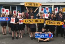 Claire Bleakley and Joseph Bolton (back left), with Featherston School pupils proudly holding up the new town signage, featuring Anzac poppies. PHOTO/SUPPLIED