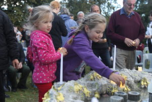 Sisters Brooklyn and Izzy Bowman lay candles for their dad Ben who died last year. PHOTO/EMILY IRELAND
